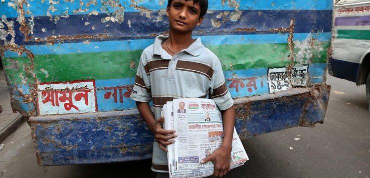 صبيًا صغيرًا يستعد لبيع جرائد الصباح في شوارع دكا في بنغلاديش